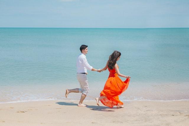 muž a žena na mořské pláži oblečení v plážovém oblečení